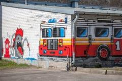 Stadsgrafitti med den brandlastbilen och brandmannen. Arkivfoton