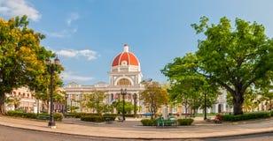 Stadshuset av den Cienfuegos staden på Jose Marti parkerar med några lokaler Royaltyfri Foto