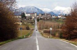 Stadsikt av Colloredo di Monte Albano, nära Udine i Italien, med den raka vägen till och med kullarna som når den Royaltyfri Fotografi