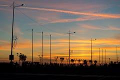 Stadskade met lantaarns, bomen en mensen backlit tegen de heldere zonsonderganghemel Royalty-vrije Stock Fotografie