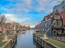 Stadskanal i Amsterdam med fartyg och tegelstenhus som reflekterar i vatten arkivfoto