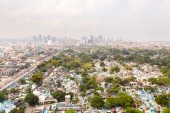 Stadskyrkogård i Manila, sikt från över Gammal kyrkogård med bostads- byggnader Stad av Manila, i soligt väder royaltyfri fotografi