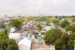 Stadskyrkogård i Manila, sikt från över Gammal kyrkogård med bostads- byggnader Stad av Manila, i soligt väder royaltyfria foton