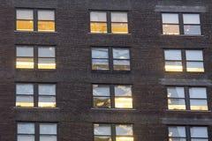 Stadslägenhetfönster på natten arkivfoton
