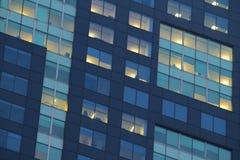 Stadslägenhetfönster på natten arkivfoto