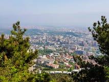 Stadslandschap met groene bomen in voorgrond op een zonnige dag stock afbeeldingen
