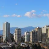 Stadslandskap med höga löneförhöjningar och berg Fotografering för Bildbyråer