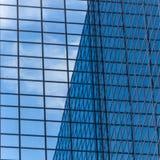 Stadslandskapet - beskåda underifrån på glass skyskrapor med reflekterad himmel i fönstren Arkivbild