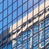 Stadslandskapet - beskåda underifrån på glass skyskrapor med reflekterad himmel i fönstren Royaltyfri Foto