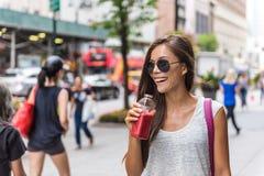 Stadslivsstilkvinna som dricker sund fruktfruktsaft royaltyfri foto