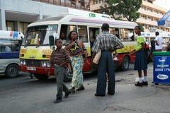 Stadslui die op openbaar vervoer op bushalte wachten stock foto's