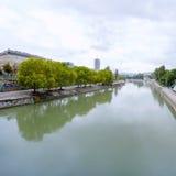 Stadsmening met rivier en bomen op rivieroever Stock Afbeeldingen
