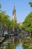 Stadsmening van Delft met kanaal en Nieuwe Kerktoren stock afbeeldingen