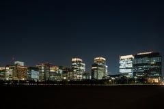 Stadsnattbelysning från många som bygger var kontorsfolk som arbetar fortfarande arkivfoton
