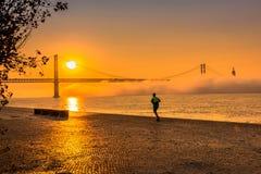 Stadsplats med en man som kör på ursnygg orange soluppgång royaltyfri fotografi