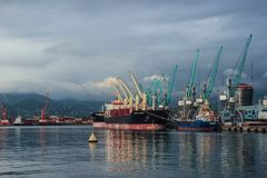 Stadsport med lastfartyg, pråm och kranar på solnedgången arkivfoto