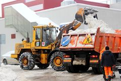 Stadsservice snöar special utrustning för borttagning efter snöfall stads- hjälpmedel Traktoren laddar snö in i lastbilen royaltyfri bild