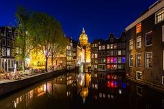 Stadssikt av Amsterdam, Nederländerna med den Amstel floden på natten royaltyfria bilder
