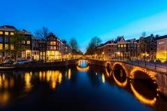 Stadssikt av Amsterdam, Nederländerna med den Amstel floden på natten arkivbild