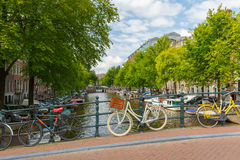Stadssikt av den Amsterdam kanalen, bron och cyklar, Holland, Neth Arkivfoton