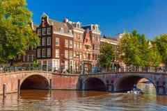 Stadssikt av den Amsterdam kanalen, bron och typisk Arkivbild
