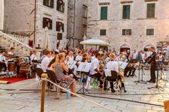 Stadssikt av folk i den gamla staden på stadfyrkanten som ser musiker som rymmer en fri utomhus- konsert i Dubrovnik royaltyfria bilder