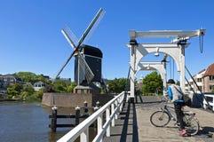 Stadssikt Leiden med klaffbron, väderkvarn, cyklist Arkivfoto