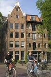 Stadssikt med kanalhus, cyklister, i Amsterdam Arkivfoto