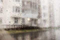 Stadssikt till och med regnigt fönster Royaltyfria Bilder