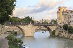 Stadssikt, välvd stenbro, Puente de los Peligros över Segur Royaltyfri Fotografi