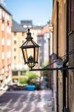 Stadssikten av ett gammalt tappninggataljus monterade på en yttre vägg i Stockholm Sverige Arkivbilder