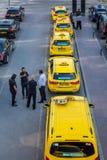 Stadssikten av många guling och svart åker taxi i linje Royaltyfria Bilder