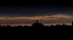 Stadssilhouet tegen donkere hemel bij dageraad Stock Fotografie
