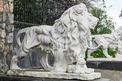Stadsskulpturer av de två vita lejonen och en lejongröngöling på ingången Lokal gränsmärke arkivfoto