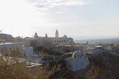 Stadssoluppgång på Santorini med en kyrka royaltyfri bild