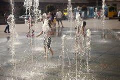 Stadsspringbrunn i sommarvärmen Barn som kör mellan vattenflöden arkivfoto