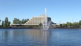 Stadsspringbrunn på bakgrunden av den hotell`-Druzhba `en, Sunny June dag russia vyborg lager videofilmer
