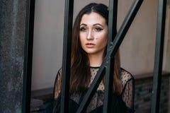 stadsstående SAD flicka Brunett i en svart klänning förväntan drömmar Stående av en ung härlig flicka Brunetten i en bl Arkivfoto