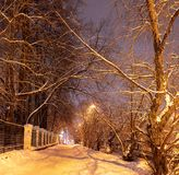 Stadssteeg met een oude omheining op een de winternacht royalty-vrije stock afbeeldingen
