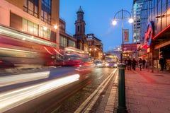 Stadstrafik på den breda gatan, Birmingham, på skymning Royaltyfria Bilder