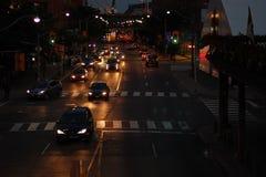 Stadstrafik på natten, billyktor och bromsljus glöder royaltyfri fotografi