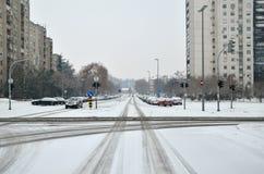 Stadstvärgata som täckas med snö Arkivfoto