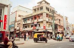 Stadsvervoer met traditionele Indische auto-riksja op straat met winkels Royalty-vrije Stock Foto's