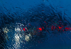 Stadsweg door regendruppels op het autowindscherm dat wordt gezien Royalty-vrije Stock Foto's