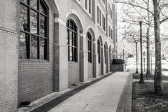 Stadt-Bürgersteig neben einem Backsteinbau mit gewölbtem Windows Lizenzfreie Stockbilder