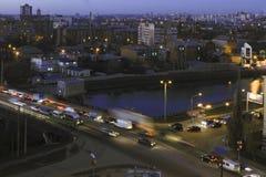 Stadt beleuchtet über dem Fluss in der blauen Stunde Lizenzfreie Stockfotos