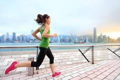 Stadt-Betrieb - Frauenläufer und Hong Kong-Skyline stockbild
