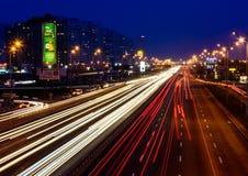 Stadt bis zum Nacht: Hauptstraßen mit Autos und Reflexionen Lizenzfreie Stockfotografie