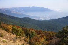 Stadt am Fuß Bear Mountains und des mehrfarbigen Waldes Lizenzfreie Stockbilder