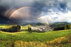 Stadt im Gebirgstal unter Regenbogen und stürmischen Wolken Stockbild